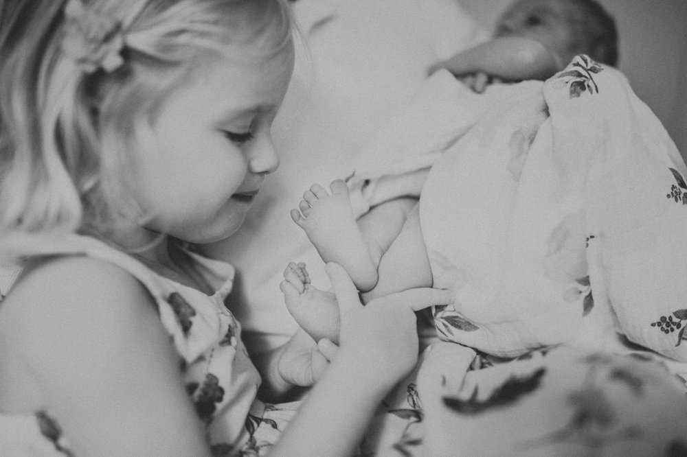 big sister holding baby girls feet | cleveland newborn lifestyle photographer