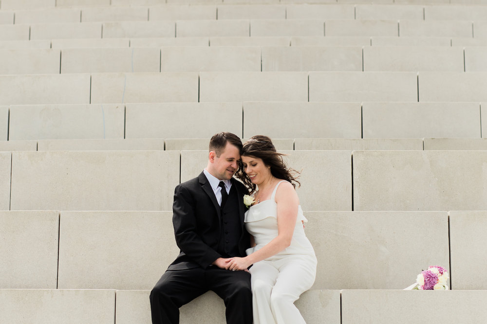 husband and wife sitting on solstice steps in lakewood park | cleveland wedding portraits