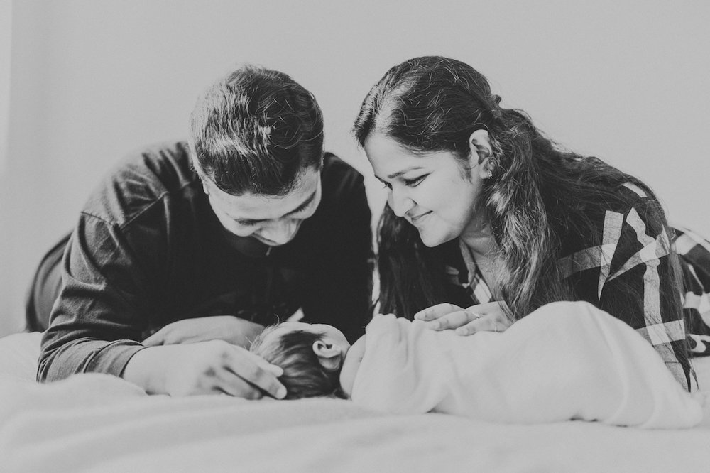 parents with infant son on bed | cleveland newborn natural portraits