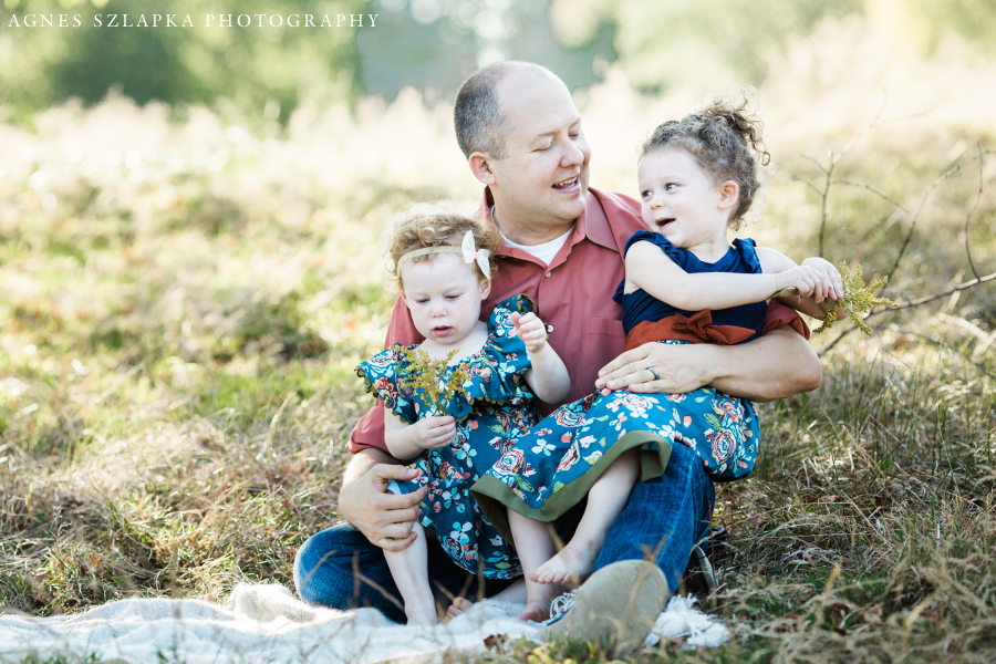 dad and his two little girls cuddling on grass | cleveland family photographer