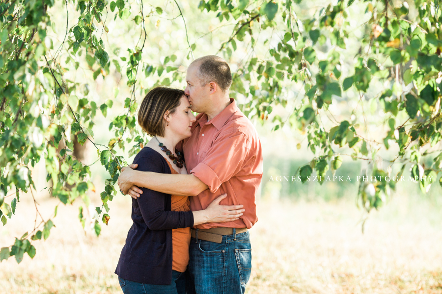 husband and wife embracing near tree branches | cleveland, OH family photographer