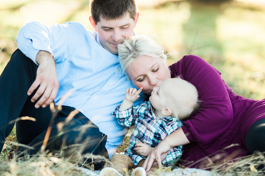 mom and dad laying on grass with baby son | cleveland family photographer