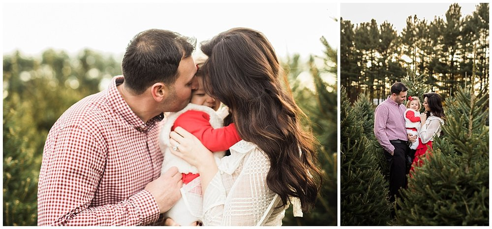 mom and dad kissing one year old daughter-christmas | cleveland, OH family photos