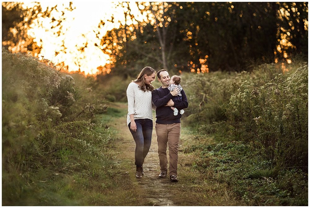 family of three walking on a nature path lakefront nature preserve | cleveland, OH newborn photos
