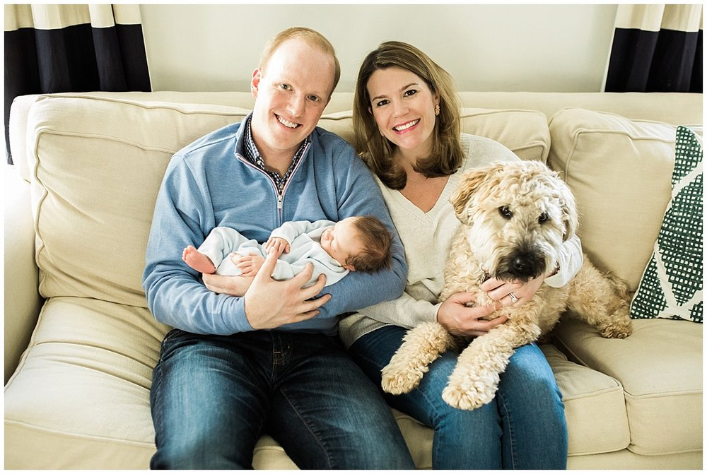 family of three and dog on living room couch | cleveland, oh newborn baby photographer