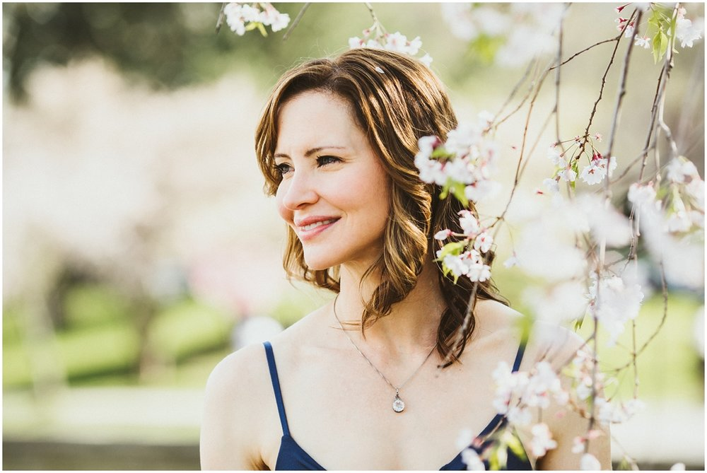 mother in blue dress amongst cherry blossoms | cleveland, oh family photographer