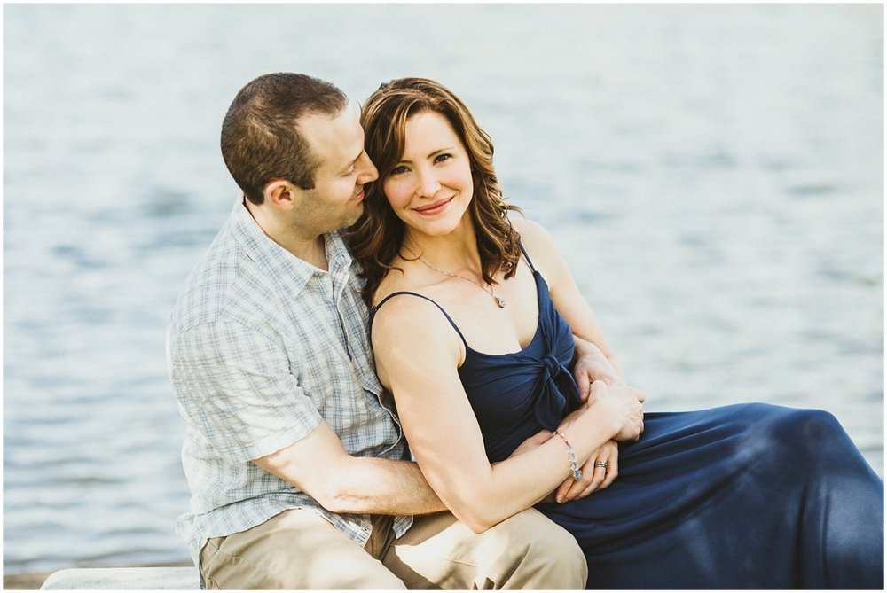 husband and with sitting on bench near pond | cleveland, OH family photographer