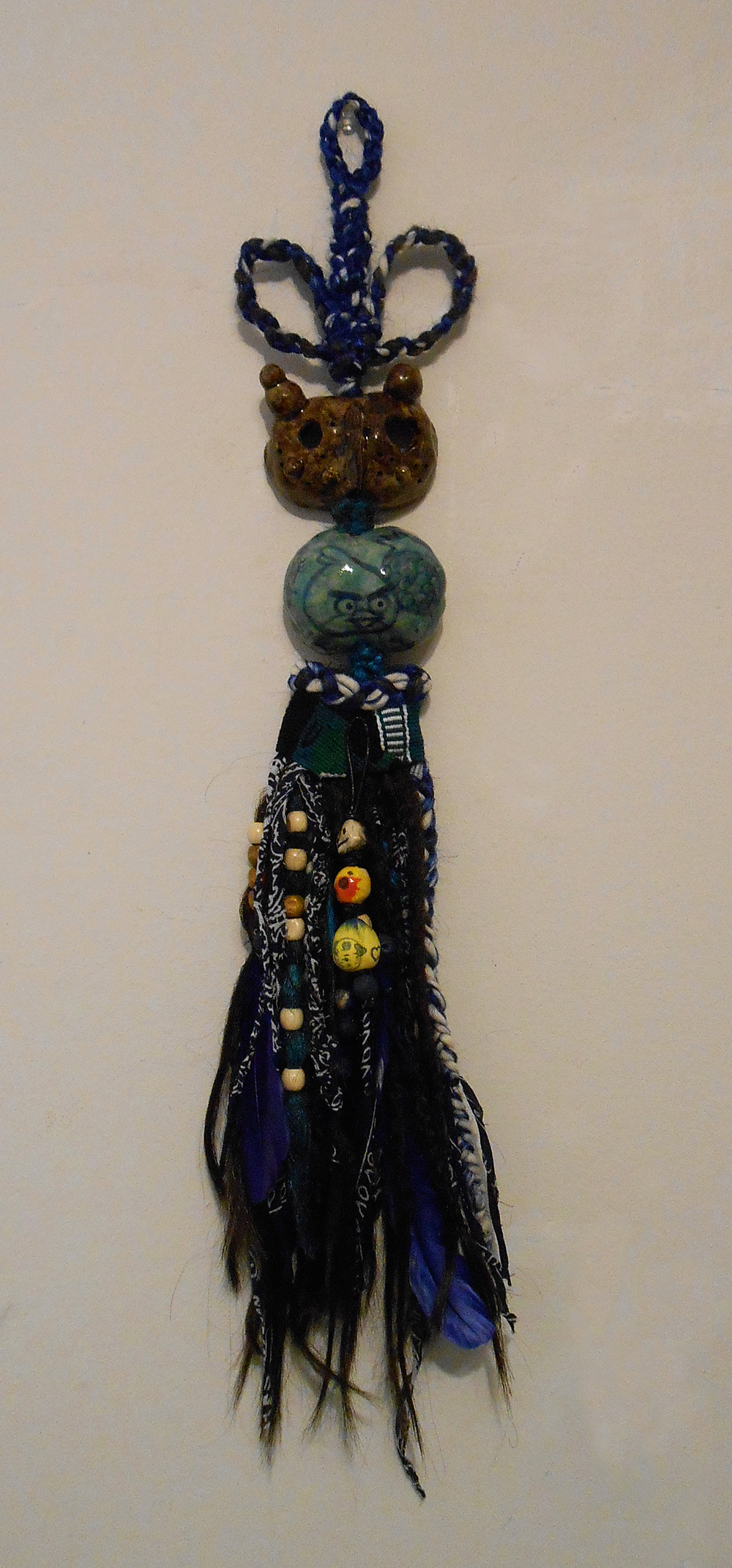 "Jiha Moon  Blue Bird  Ceramic, hand-knotted synthetic hair, feathers, fabric, wooden beads, found objects 28"" x 5"" x 2.5"" 2014"