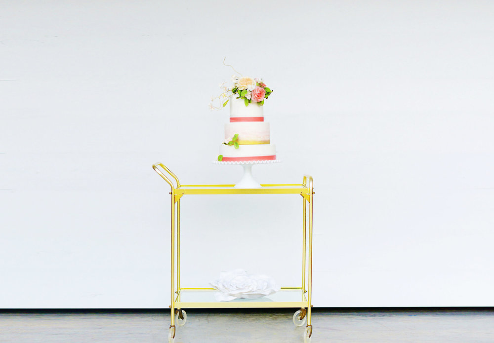 tiered pink watercolor wedding cake on stand.jpg