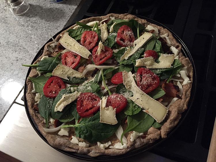Spinach, tomato, onion and brie pizza.