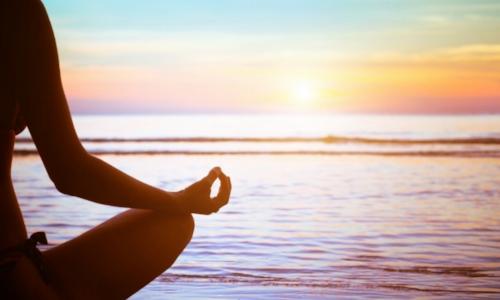 Yogi sitting at beach sunset