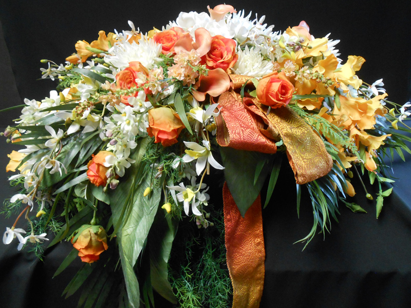 Orange and white casket spray
