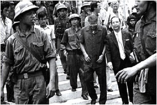 """Ngày 30 tháng 4 tại Sài gòn bộ đội Việt Cộng áp giải Dương văn Minh mặc """"đồ lớn ba túi""""mặt cúi gầm đi cạnh Vũ Văn Mẫu  (ngoại trưởng)  mặc quần áo Tây phương  tề chỉnh - tưởng là thời cơ đã tới rồi, đi tiếp xúc với """"những người anh em phía bên kia"""" (?)"""