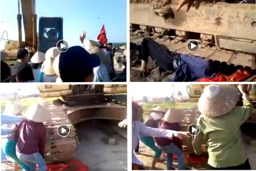 Xe ủi đất cướp nhà dân lạnh lùng cán lên người đàn bà bị cướp đất cầm cờ đỏ sao vàng chống đối. Hình ảnh lấy từ video do chùa Tầm Nguyên đưa lên mạng điện tử.