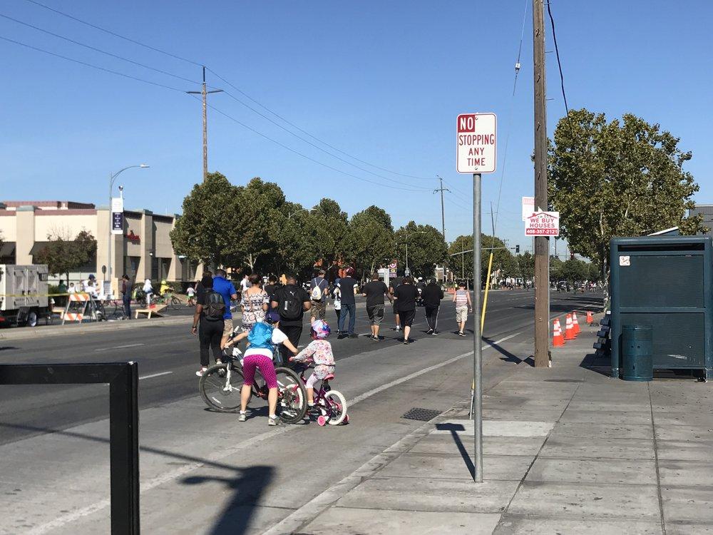 Mẹ dắt con xuống đường tập lái xe đạp.