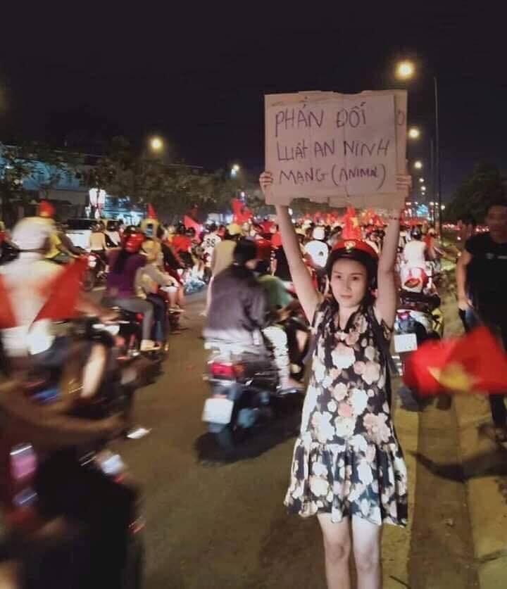 """Cô gái cầm bảng """"phản đối an ninh mạng"""" ngay trên đường phố mà người dân đang ăn mừng VN thắng Philippinrs trong trận Cup 2018. Nguồn Facebook. FB Cường Phạm share post của FB Oanh Bùi."""