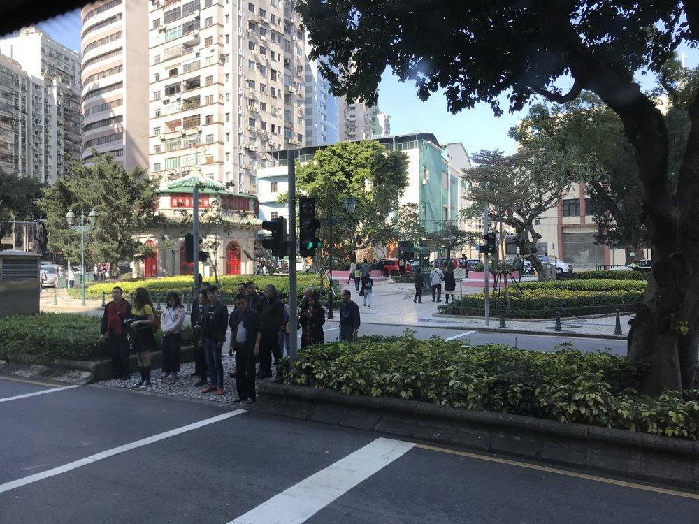 Người bộ hành đang đứng đợi để băng qua một con đường tại ngoại ô Macau.