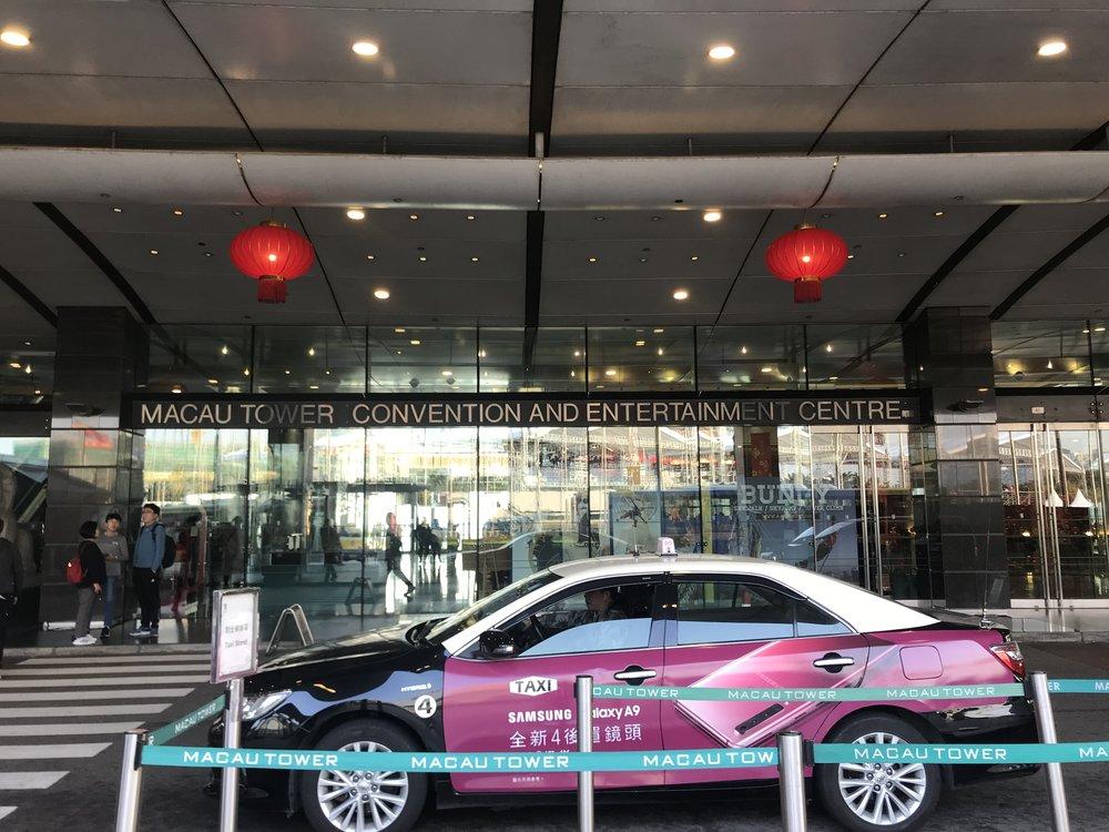 Du khách xuống xe bus để vào thăm trung tâm giải trí và hội nghị của tòa Tháp Macau.