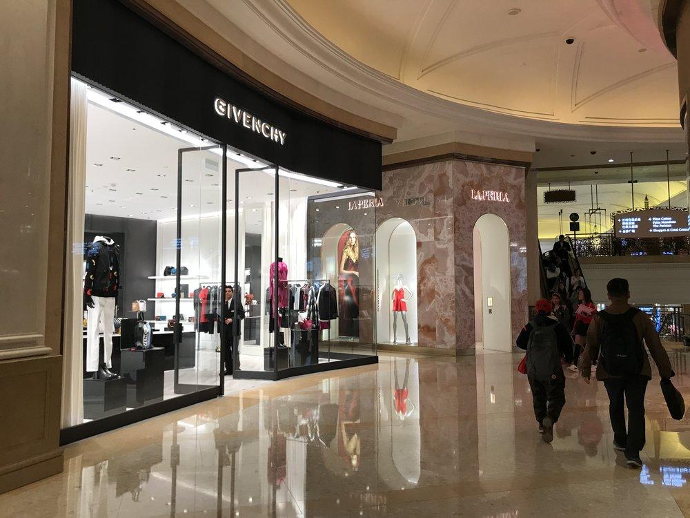 Đi bộ ngang các cửa tiệm mua sắm trong khách sạn Parisian Macau.
