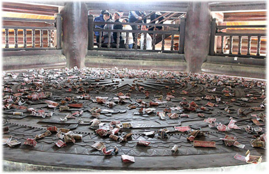 Người đi lễ chùa Bái Đính (Ninh Bình) ném tiền lẻ xuống trống đồng đề cầu may mắn khiến trống đồng như một nơi chứa rác