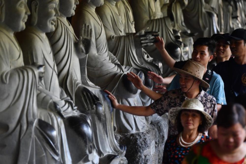 Người dân xoa tay vào các tượng Phật.