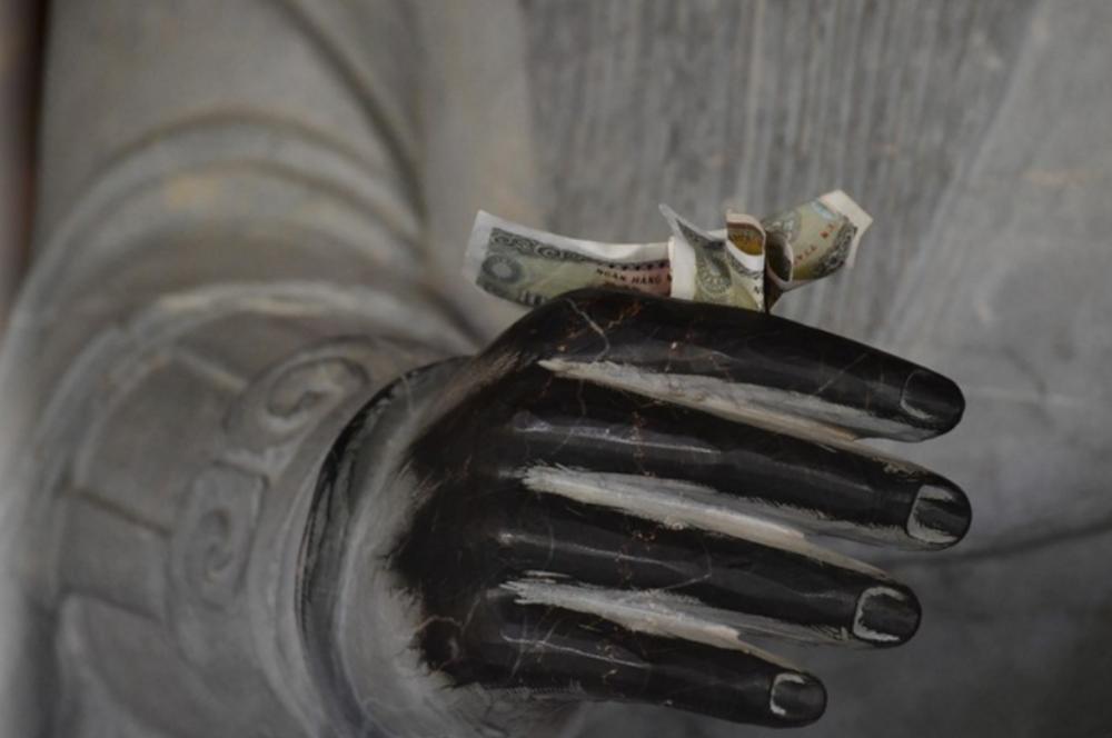 Người đi lễ chùa nhét tiền vào tay Phật để xin phước lộc.