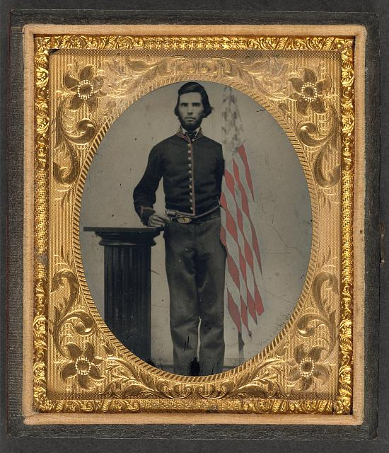 Soldier in Union Artillery Uniform Standing Next to Pedestal Holding Revolver and American Flag | Circa 1861-1865