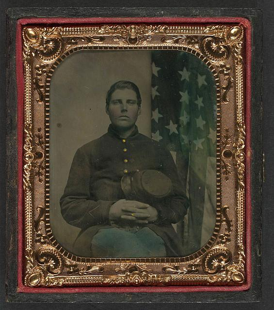 Soldier in Uniform with Forage Cap in Front of American Flag | Circa 1861-1865