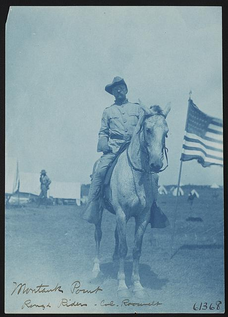 Teddy Roosevelt Wearing Rough Rider Uniform and Sitting on a Horse with an American Flag | Circa 1898