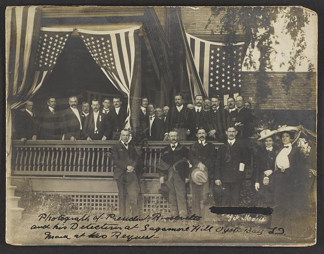 President Roosevelt and His Detectives at Sagamore Hill Posing on a Porch with Flags | Circa 1902