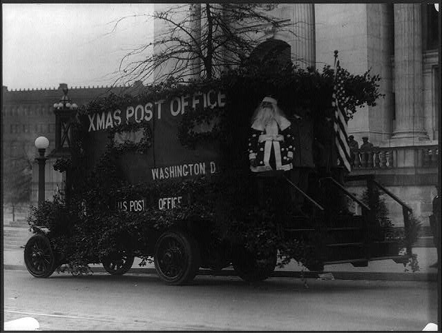 Santa Claus on the Back of a Washington D.C. Post Office Truck Decorated with Branches and an American Flag | Circa 1909