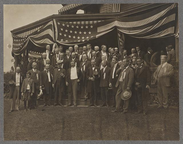 Teddy Roosevelt Standing in Center of a Group of Men Outside a Porch Draped with Flags | Circa 1904