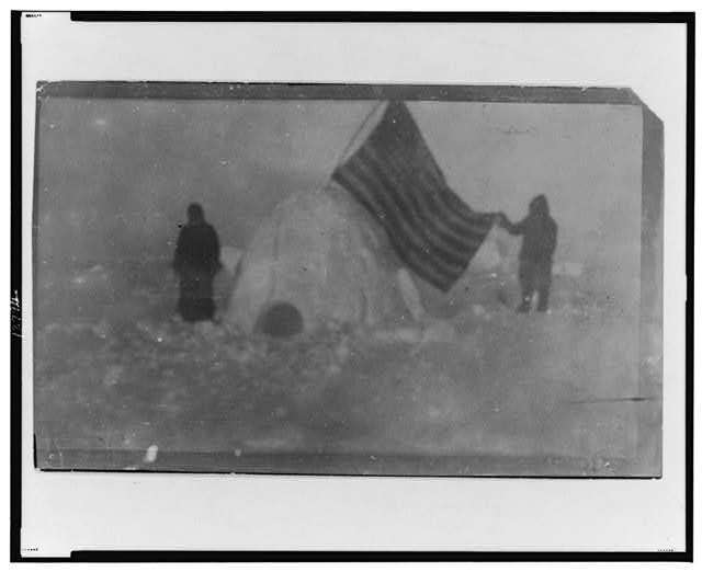 Two Members of Frederick Cook's Expedition with US Flag Stuck in Igloo at Expedition Camp Site at the North Pole | Circa 1909