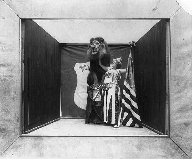Woman with Stars and Eagle on Her Costume Holding a US Flag and Touching Tame Lion | Circa 1901