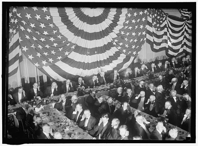 Banquet Scene with Flag Draping and Men Seated Holding Up Listening Device to One Ear | Circa 1913