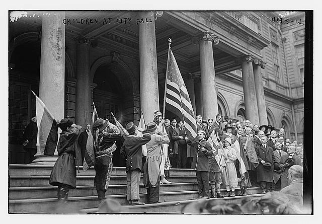 Children with Flags of Different Countires as a Woman Stands with an American Flag on the Steps of City Hall in New York City During an Americanaization Rally | Circa 1917