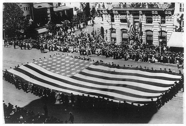 Huge Flag Being Carried by a Large Group of Men in a GAR Parade in Washington D.C. | Circa 1915