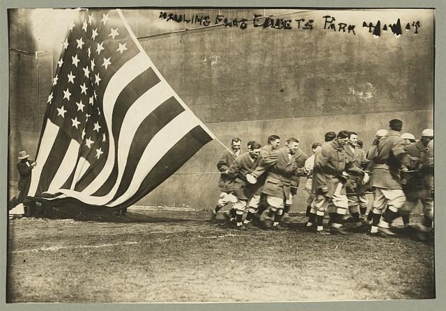 Group of Men Raising Large American Flag on Opening Day of the Baseball Season at Ebbets Field | Circa 1914