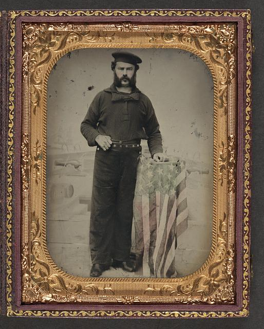 Sailor in Union Uniform at American Flag Draped Table in Front of Painted Backdrop Showing Naval Ship | Circa 1861-1865