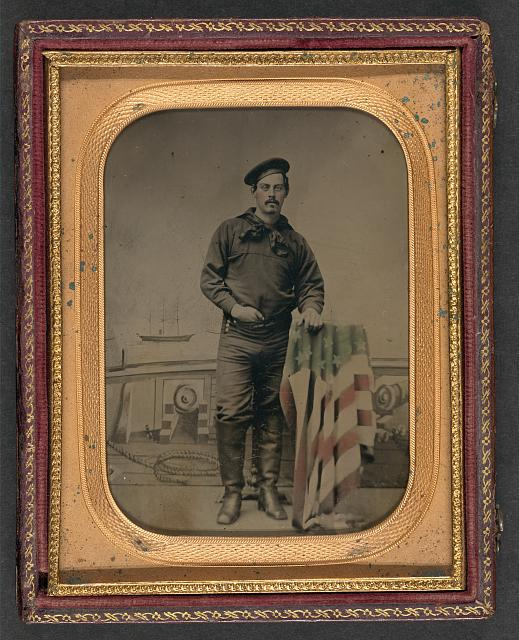 Sailor in Union Uniform Resting Hands on American Flag-Draped Table in Front of Painted Backdrop Showing Naval Scene | Circa 1861-1865