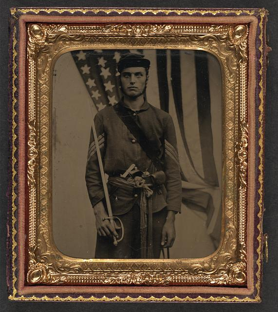 Soldier in Union Sergeant Uniform and Sash with Model 1840 Non-Commissioned Officer's Sword, Revolver, Cap Box, and Knife in Front of American Flag | Circa 1861-1865