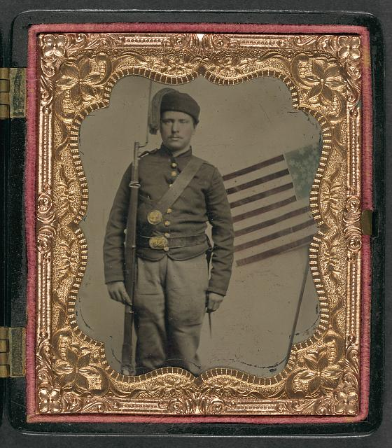 Soldier in Union Uniform with Bayoneted Musket in Front of Painted Backdrop Showing American Flag | Circa 1861-1865