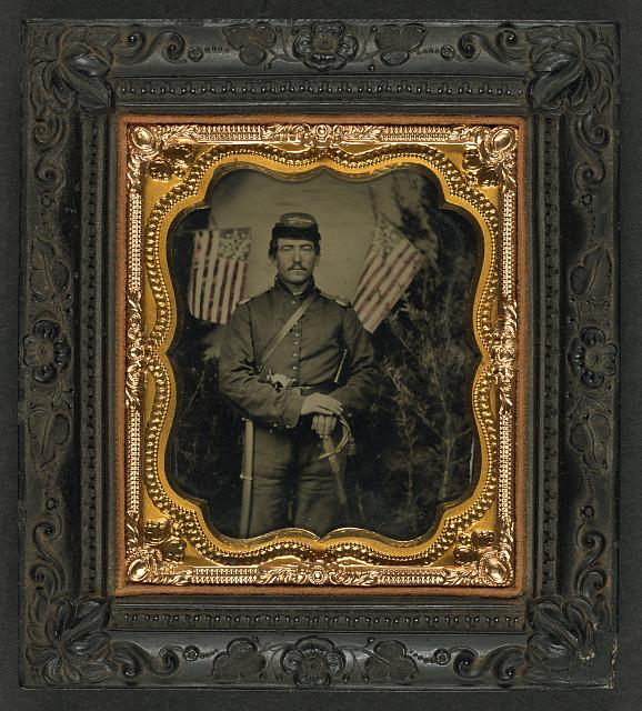 Soldier in Union Uniform with Shoulder Scales with Pearl-Handed Revolver and Saber in Front of Backdrop Showing Trees and Two Great Star Flags | Circa 1861-1865