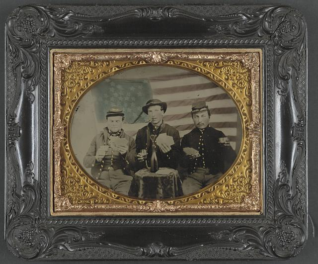 Three Soldiers Playing Cards, Smoking, and Drinking in Front of the American Flag | Circa 1861-1865