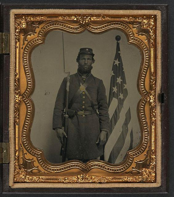 Soldier in Union Uniform and Company H Cap with Bayoneted Musket, Cap Box, and Volunteer Main Militia Belt Buckle in Front of American Flag | Circa 1861-1865