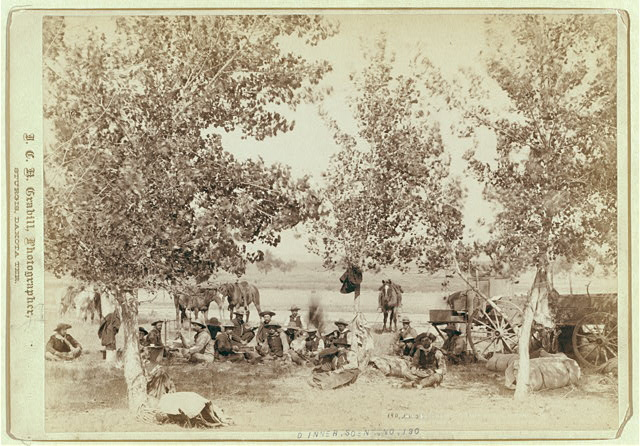 Cowboys Eating Dinner, Seated on the Ground Near Trees | Circa 1887