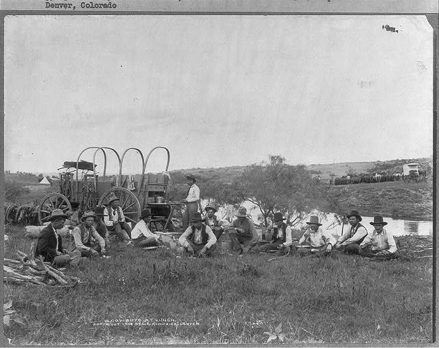 Cowboys from the JA Ranch in the Panhandle of Texas, Seated Next to Chuckwagon and Photographer's Wagon | Circa 1904