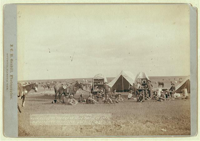 Cowboys Seated Around Chuckwagon at Campsite | Circa 1887