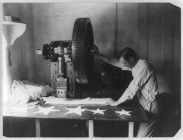 Man Cutting Out Stars for a Flag with a Machine