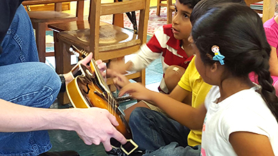 A few children practice strumming.